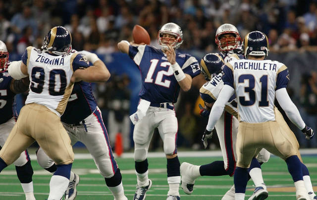 FILE - In this Feb. 3, 2002, file photo, New England Patriots quarterback Tom Brady (12) throws a pass  as St. Louis Rams' Jeff Zgonina (90) and Adam Archuleta (31) rush during the third quarter of Super Bowl XXXVI at the Louisiana Superdome in New Orleans. The Patriots are 5-2 in Super Bowls with Tom Brady. So when folks wonder why the spread against Philadelphia is between 5 and 6 points, they should consider that the total difference in scoring in those seven games is 12 points: Patriots 169, opponents 157.  (AP Photo/Doug Mills, File)