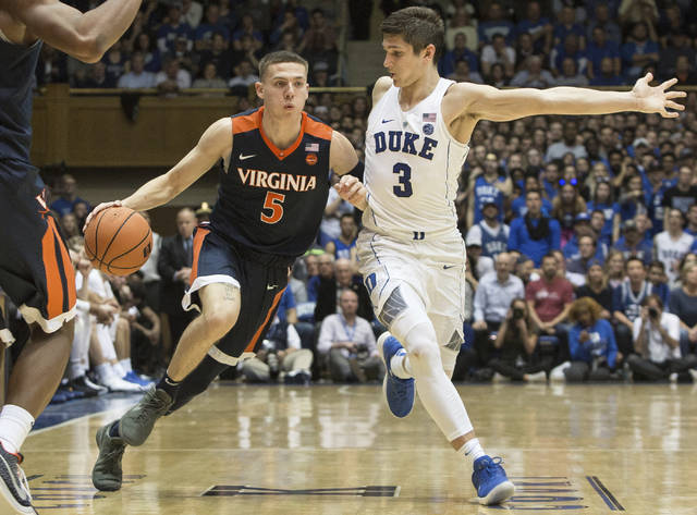 Virginia's Kyle Guy (5) handles the ball against the defense of Duke's Grayson Allen (3) during the second half of an NCAA college basketball game in Durham, N.C., Saturday, Jan. 27, 2018. Virginia defeated Duke 65-63. (AP Photo/Ben McKeown)