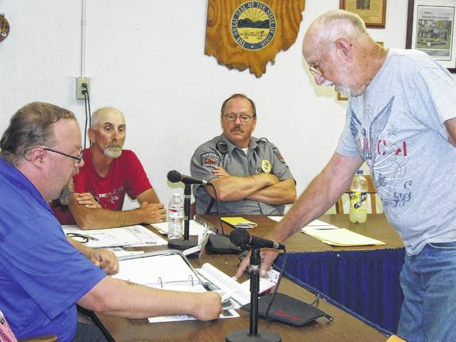 Larry Fair, right foreground, points to a map in connection with a property dispute at a June 2016 session of Sabina Village Council. From left are Councilman Jim Mongold, Sabina Village Administrator Rob Dean and Sabina Police Chief Keynon Young.