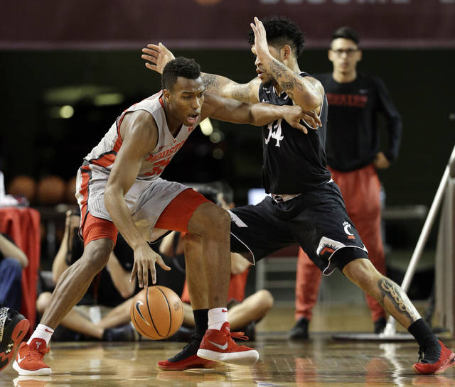 Houston forward Fabian White Jr. (35) looks for a way around Cincinnati guard Jarron Cumberland (34) during the first half of an NCAA college basketball game Thursday, Feb. 15, 2018, in Houston. (AP Photo/Michael Wyke)