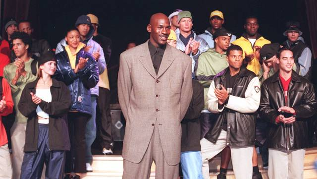 FILE - In this March 2,1999, file photo, Michael Jordan stands with a group of models at the Bellagio Hotel in Las Vegas where he previewed the Fall/Holiday 1999 Jordan collection, a sub-brand of Nike. By the 1980s, America finally publicly embraced the black athlete, looking past skin color to see athleticism and skill, rewarding stars with multimillion-dollar athletic contracts, movie deals, lucrative shoe endorsements and mansions in all-white enclaves. Who didn't want to be like Mike? (Jim Laurie/Las Vegas Review-Journal via AP, File)