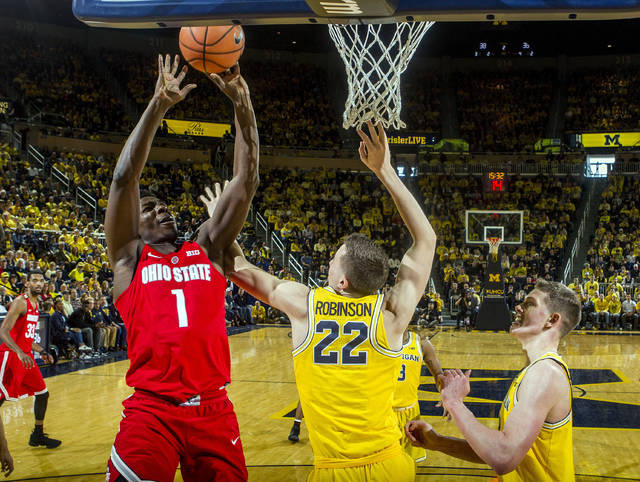 Ohio State forward Jae'Sean Tate (1) attempts a basket while defended by Michigan guard Duncan Robinson (22) and forward Moritz Wagner, right, in the second half of an NCAA college basketball game at Crisler Center in Ann Arbor, Mich., Sunday, Feb. 18, 2018. (AP Photo/Tony Ding)