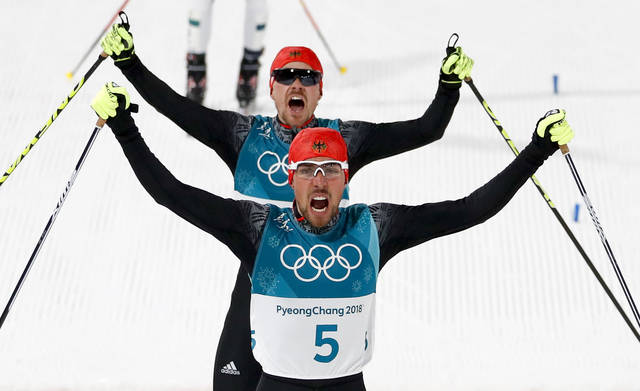 Johannes Rydzek, of Germany, celebrates after winning the gold medal ahead of silver medalist Fabian Riessle, of Germany, in the men's 10km cross-country skiing competition during the nordic combined event at the 2018 Winter Olympics in Pyeongchang, South Korea, Tuesday, Feb. 20, 2018. (AP Photo/Matthias Schrader)