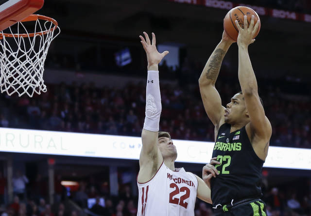 Michigan State's Miles Bridges, right, shoots over Wisconsin's Ethan Happ during the first half of an NCAA college basketball game Sunday, Feb. 25, 2018, in Madison, Wis. (AP Photo/Andy Manis)