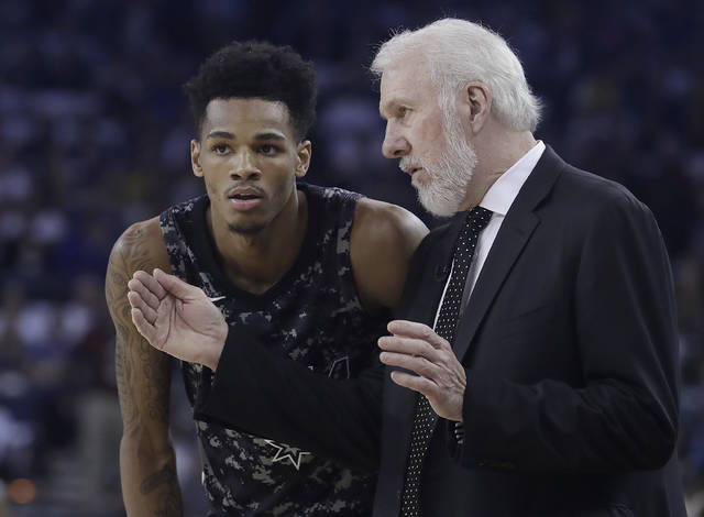 San Antonio Spurs head coach Gregg Popovich, right, talks with Dejounte Murray during the first half of an NBA basketball game against the Golden State Warriors in Oakland, Calif., Thursday, March 8, 2018. (AP Photo/Jeff Chiu)