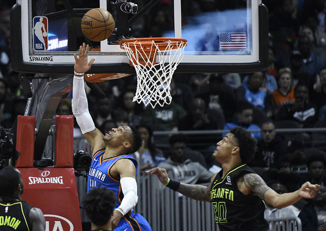 Oklahoma City Thunder guard Russell Westbrook shoots a reverse layup as Atlanta Hawks forward John Collins (20) defends during the first half of an NBA basketball game, Tuesday, March 13, 2018, in Atlanta. (AP Photo/John Amis)