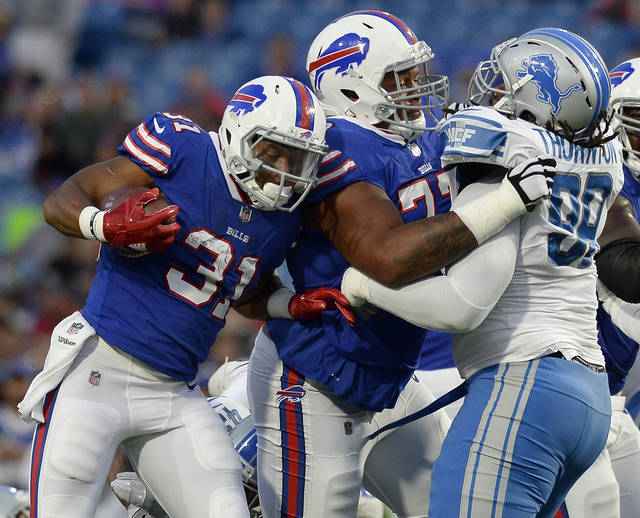 FILE - In this Aug. 31, 2017, file photo, Buffalo Bills running back Jonathan Williams (31) follows the block of tackle Cordy Glenn (77) against Detroit Lions defensive tackle Khyri Thornton (99) during the first half of a preseason NFL football game in Orchard Park, N.Y. A person familiar with the deal has told The Associated Press the Bills have moved up nine spots in the draft by swapping first-round draft picks with the Cincinnati Bengals, who also acquired high-priced left tackle Glenn as part of the trade. (AP Photo/Adrian Kraus, File)