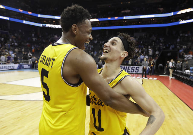 UMBC's K.J. Maura (11) and Jourdan Grant (5) celebrate the team's 74-54 win over Virginia in a first-round game in the NCAA men's college basketball tournament in Charlotte, N.C., Friday, March 16, 2018. (AP Photo/Gerry Broome)