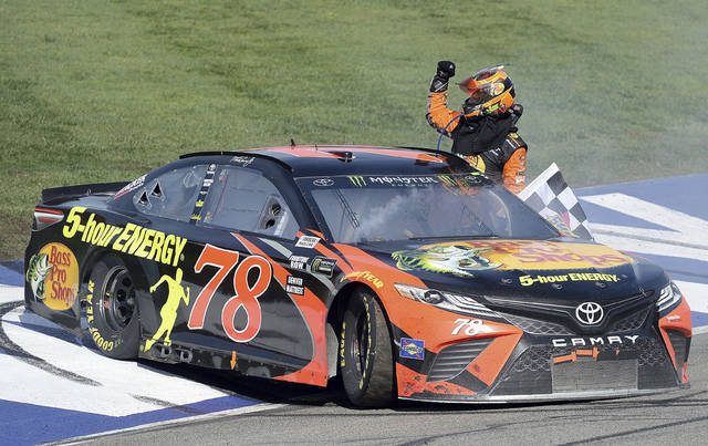 Martin Truex Jr. celebrates after winning the NASCAR 400 mile auto race Sunday, March 18, 2018, at Auto Club Speedway in Fontana, Calif. (AP Photo/Will Lester)