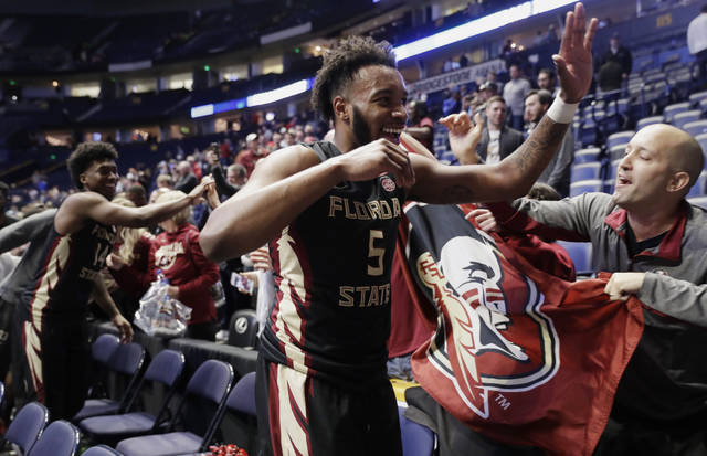 Florida State guards PJ Savoy (5) and Terance Mann (14) are congratulated by fans after defeating Xavier in a second-round game in the NCAA college basketball tournament in Nashville, Tenn., Sunday, March 18, 2018. Florida State defeated Xavier 75-70. (AP Photo/Mark Humphrey)