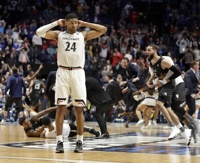 Cincinnati forward Kyle Washington (24) stands on the court as the Nevada team celebrates during the end of the second half of a second-round game in the NCAA college basketball tournament in Nashville, Tenn., Sunday, March 18, 2018. Nevada defeated Cincinnati 75-73. (AP Photo/Mark Humphrey)