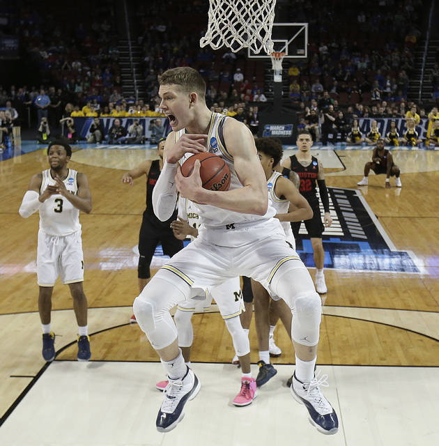 Michigan forward Moritz Wagner (13) grabs a rebound during the second half of the team's NCAA men's college basketball tournament second-round game against Houston on Saturday, March 17, 2018, in Wichita, Kan. Michigan won 64-63. (AP Photo/Charlie Riedel)
