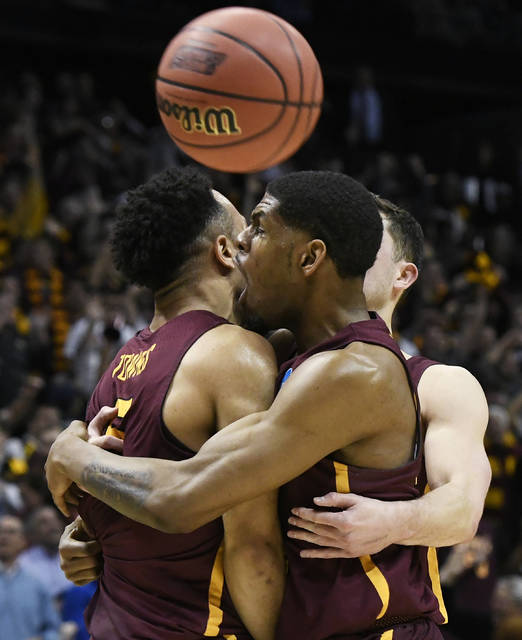 Loyola-Chicago guard Marques Townes, left, his embraced my teammates after his three-point shot against Nevada during the second half of a regional semifinal NCAA college basketball game, Thursday, March 22, 2018, in Atlanta. Loyola-Chicago won 69-68. (AP Photo/John Amis)