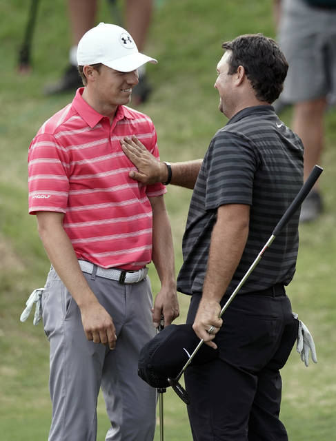 Jordan Spieth, left, is patted on the chest by opponent Patrick Reed, right, after losing the round in round-robin play at the Dell Technologies Match Play golf tournament, Friday, March 23, 2018, in Austin, Texas. (AP Photo/Eric Gay)