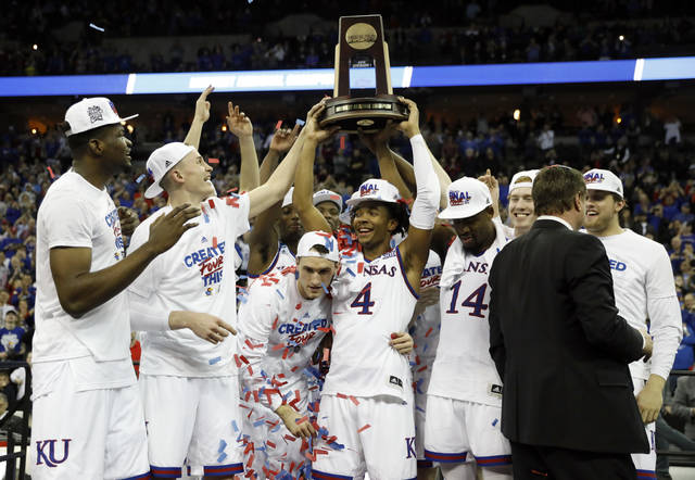 Kansas' Devonte' Graham (4) holds the trophy after defeating Duke in a regional final game in the NCAA men's college basketball tournament Sunday, March 25, 2018, in Omaha, Neb. Kansas won 85-81 in overtime. (AP Photo/Charlie Neibergall)