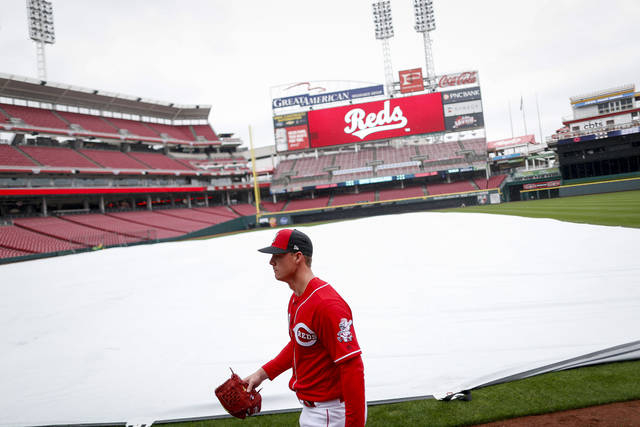 Cincinnati Reds pitcher Austin Brice walks back to the dugout after working out at Great American Ballpark, Thursday, March 29, 2018, in Cincinnati. Their first game of the regular season against the Washington Nationals was postponed until Friday due to weather. (AP Photo/John Minchillo)