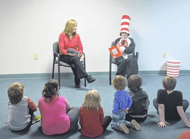 "MacKenzie Pyle dressed as the Cat in the Hat reads ""Green Eggs and Ham"" to guests at Wilmington Public Library's Dr. Seuss Birthday Party on Thursday."