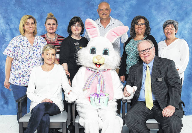 In the staff photo are, from left: seated, Kelly Strunk, DON; Easter Bunny (Jenny Dobbs, volunteer); and Tom Cunningham, Executive Director; standing, Lori Evans, ADON; Angie Byrom Brown, Social Services; Lisa Beach, Activity Director; Mark Wells, Environmental Services; Bonnie Rose, Business Office Manager; and Tracy Damewood, HR/Community Marketing.