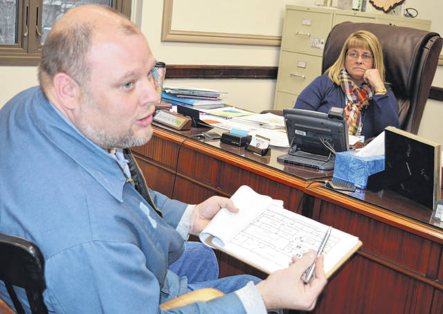 Holding a diagram of a county-owned facility Wednesday, Clinton County Maintenance Director Jeff Williams, left foreground, will have a busy year as multiple county departments begin moving to alternate spaces. Listening in the background is Clinton County Commissioner Brenda K. Woods.