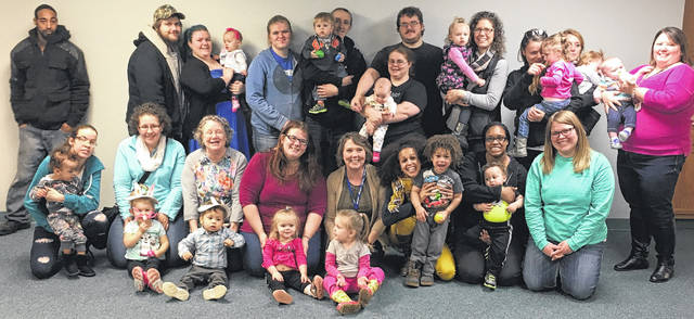 Families of young children, Help Me Grow home visiting and Early Intervention staff take a break from their playgroup at the Wilmington Public Library on March 15 to pose for a photo.