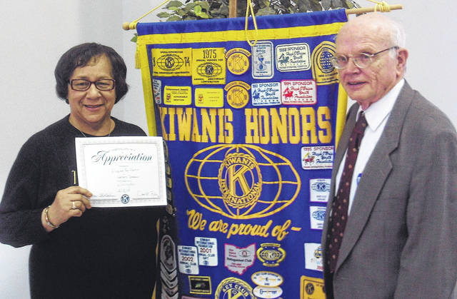 Executive Director of Harvest of Gold, Eleanor Harris, receives a Kiwanis certificate and pen from Wilmington Club President Mack Fife for being the Kiwanis Club program speaker .