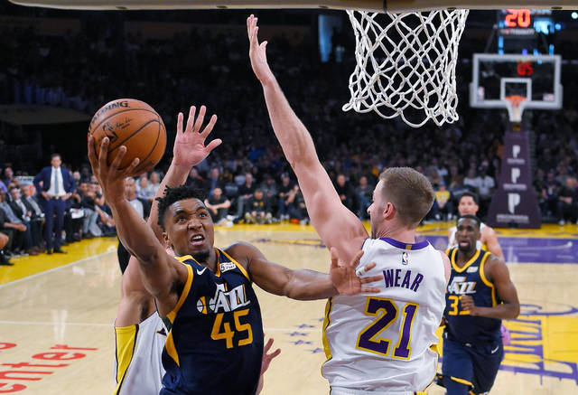 Utah Jazz guard Donovan Mitchell, left, shoots as Los Angeles Lakers forward Travis Wear defends during the first half of an NBA basketball game Sunday, April 8, 2018, in Los Angeles. (AP Photo/Mark J. Terrill)