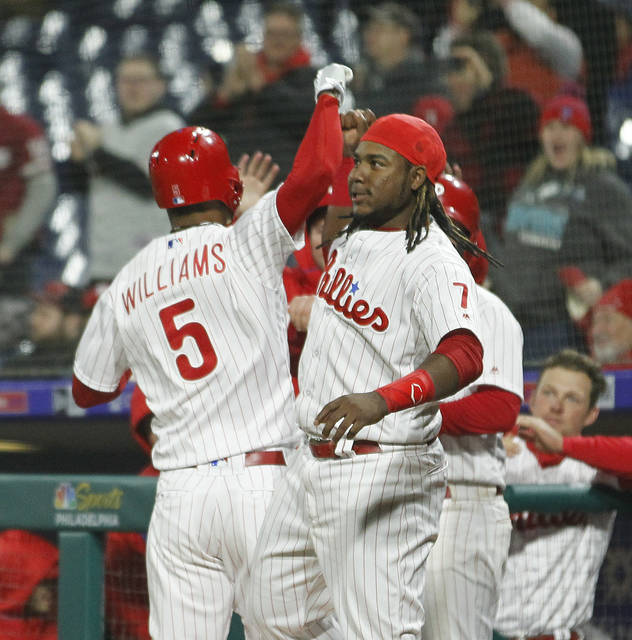 Philadelphia Phillies' Nick Williams, left, is greeted at the dugout after hitting a solo home run during the eighth inning of a baseball game against the Cincinnati Reds, Monday, April 9, 2018, in Philadelphia, Pa. (AP Photo/Tom Mihalek)