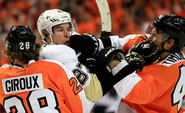 "FILE - In this April 15, 2012, file photo, Philadelphia Flyers Claude Giroux, left, holds on to Pittsburgh Penguins' Sidney Crosby as Kimmo Timonen, right, lands a punch to Crosby's jaw during the first period of Game 3 in a first-round NHL Stanley Cup playoffs hockey series in Philadelphia. The NHL's divisional playoff format was brought back specifically to ignite old and create new rivalries, which has been a successful venture even if hate looks different than it did in the days of the ""Broad Street Bullies."" Playoff rivalries are no longer about dropping the gloves or even laying out bone-crushing hits like in past eras. (AP Photo/Tom Mihalek, File)"