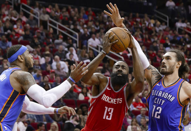 Houston Rockets guard James Harden (13) drives for a shot between Oklahoma City Thunder forward Carmelo Anthony, left, and center Steven Adams (12) during the second half of an NBA basketball game Saturday, April 7, 2018, in Houston. (AP Photo/Michael Wyke)