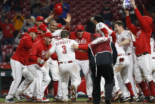 Cincinnati Reds' Scooter Gennett (3) celebrates with his teammates after hitting a two-run walk-off home run off Atlanta Braves relief pitcher Max Fried during the 12th inning of a baseball game Tuesday, April 24, 2018, in Cincinnati. (AP Photo/John Minchillo)