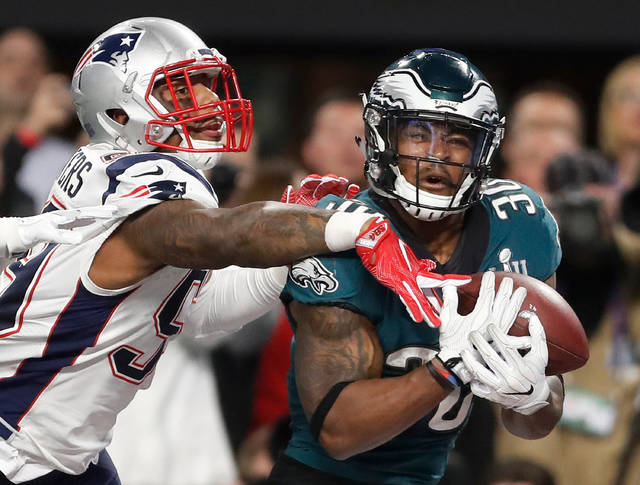 FILE - In this Feb. 4, 2018, file photo, Philadelphia Eagles' Corey Clement, right, catches a touchdown pass in front of New England Patriots' Marquis Flowers during the second half of the NFL Super Bowl 52 football game in Minneapolis. While first-round picks receive most of the attention and players chosen the first two days of the draft get more money and better job security, success on Day 3 of the draft often separates the elite teams from the good ones. That was evident when the Eagles and Patriots met in February. Corey Clement had 100 yards receiving and one touchdown and LeGarrette Blount ran for 90 yards and one touchdown in Philadelphia's 41-33 victory. Danny Amendola led the Patriots with 152 yards receiving and Chris Hogan had 128. All four players were undrafted free agents. (AP Photo/Jeff Roberson, File)