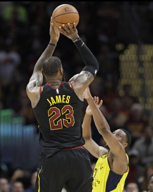 Cleveland Cavaliers' LeBron James (23) shoots a game-winning three point shot over Indiana Pacers' Thaddeus Young (21) in the second half of Game 5 of an NBA basketball first-round playoff series, Wednesday, April 25, 2018, in Cleveland. The Cavaliers won 98-95. (AP Photo/Tony Dejak)