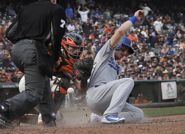 Los Angeles Dodgers' Cody Bellinger, right, scores next to San Francisco Giants catcher Nick Hundley during the eighth inning of a baseball game in San Francisco, Saturday, April 28, 2018. (AP Photo/Jeff Chiu)