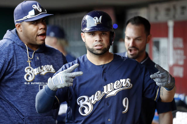 Milwaukee Brewers' Manny Pina (9) celebrates in the dugout after hitting a solo home run off Cincinnati Reds starting pitcher Brandon Finnegan in the fourth inning of a baseball game, Monday, April 30, 2018, in Cincinnati. (AP Photo/John Minchillo)