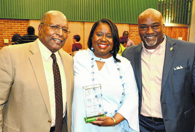 Art Brooks, left, and Chip Murdock congratulate Sigrid Solomon as the inaugural recipient of Wilmington College's Art Brooks Award of Diversity Excellence.