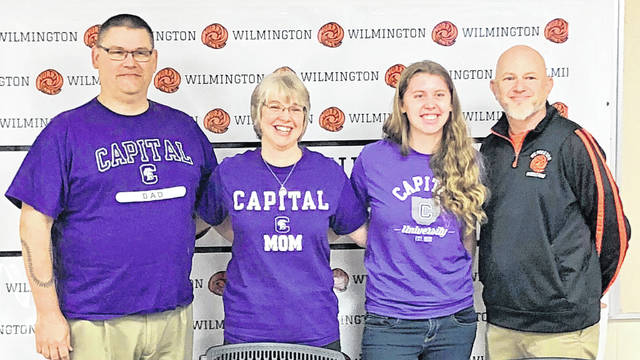 Wilmington High School senior Heather Fryman will continue her education at Capital University and plans to run for the Crusaders cross country team. In the photo, from left to right, father Jeff Fryman, mother June Fryman, Heather Fryman, and WHS cross country and track and field coach Brad Heys.