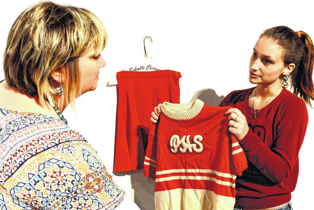 Senior Alicia Gifford, right, hangs a cheerleading outfit in the QHC Gallery while survivor advocate Sarah Martin looks on. The compelling story behind the clothing is its owner was sexually assaulted by a football player at her high school.