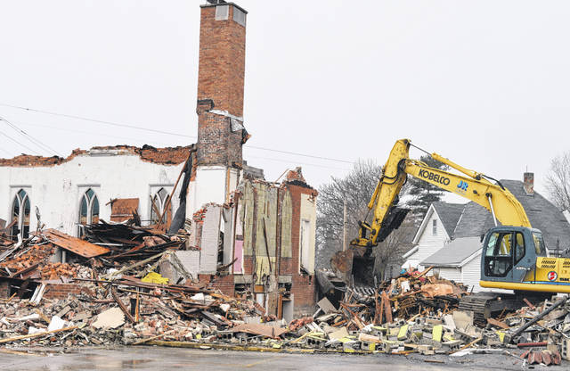 After demolition, site cleanup will begin at the Washington Street spot where the Sabina Church of Christ building stood for 138 years. Pictured is flattening of the facility that occurred Monday. For more photos, please visit wnewsj.com .