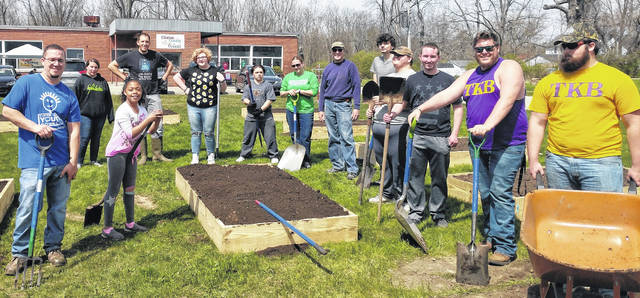 Members of Wilmington College's TKB Fraternity, Clinton County Master Gardeners and CCYC students pause after a job well done building community gardens.