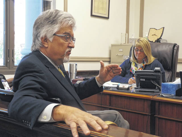 """On Monday, Clinton County Common Pleas Judge John W. """"Tim"""" Rudduck, foreground, discusses adult probation staffing trends and the need for privacy between a supervision officer and the defendant. County Commissioner Brenda K. Woods is in the photo's background."""