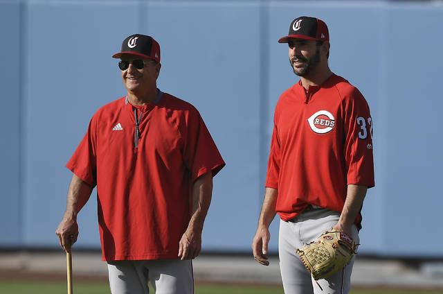 Cincinnati Reds interim manager Jim Riggleman, left, talks with Matt Harvey prior to the team's baseball game against the Los Angeles Dodgers on Thursday, May 10, 2018, in Los Angeles. (AP Photo/Mark J. Terrill)