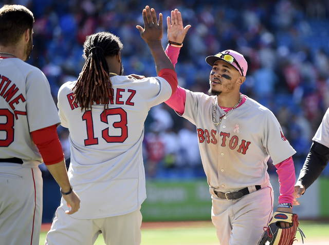 Boston Red Sox right fielder Mookie Betts, right, celebrates with teammate Hanley Ramirez (13) after defeating the Toronto Blue Jays in baseball game action in Toronto, Sunday, May 13, 2018. (Nathan Denette/The Canadian Press via AP)