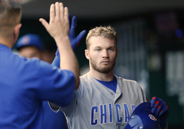 Chicago Cubs' Ian Happ, right, is congratulated in the dugout following a solo home run off Cincinnati Reds starting pitcher Sal Romano during the fourth inning in the second baseball game of a doubleheader, Saturday, May 19, 2018, in Cincinnati. (AP Photo/Gary Landers)