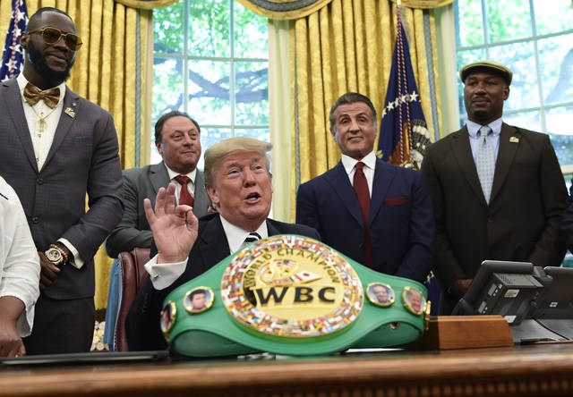 President Donald Trump, center, speaks as he posthumous pardons Jack Johnson, boxing's first black heavyweight champion, during an event in the Oval Office of the White House in Washington, Thursday, May 24, 2018. Trump is joined by, from left, heavyweight champion Deontay Wilder, Keith Frankel, Sylvester Stallone, and former heavyweight champion Lennox Lewis. (AP Photo/Susan Walsh)