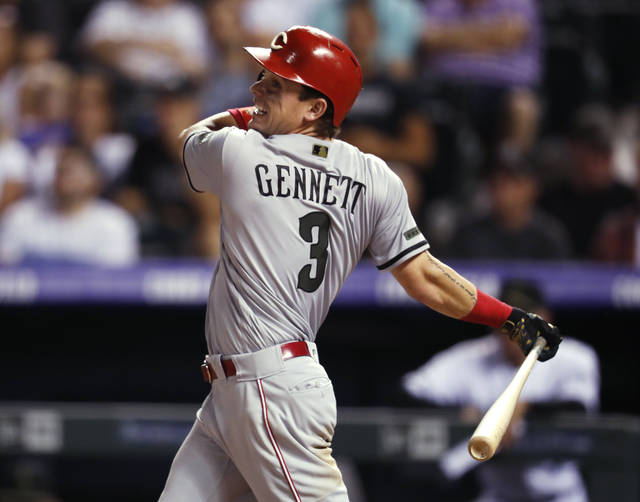 Cincinnati Reds' Scooter Gennett watches his single off Colorado Rockies relief pitcher Jake McGee during the ninth inning of a baseball game Saturday, May 26, 2018, in Denver. The Reds won 6-5. (AP Photo/David Zalubowski)