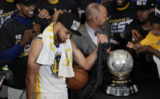 Golden State Warriors guard Stephen Curry celebrates with teammates as they receive their trophy after defeating the Houston Rockets in Game 7 of the NBA basketball Western Conference finals, Monday, May 28, 2018, in Houston. (AP Photo/David J. Phillip)