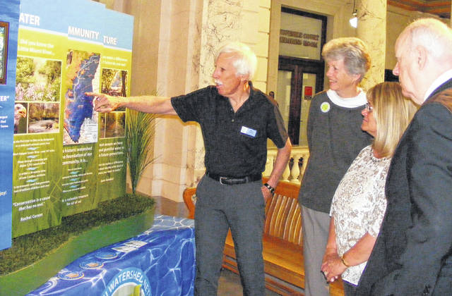 A display regarding the Little Miami Watershed Network was set up temporarily Monday in the courthouse. From left are Bill Schieman with the Little Miami Watershed Network, Hope Taft, and Clinton County Commissioners Brenda K. Woods and Patrick Haley.