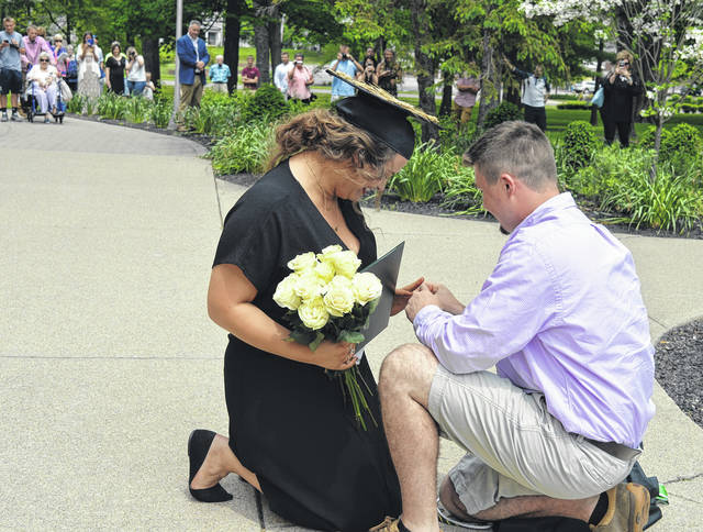 Baylah Arehart of Clinton County, left foreground, graduated Saturday from Wilmington College. After commencement ended, she and Kelly Penquite, a previous WC graduate, took a final stroll on Collett Mall and when they reached College Hall, Penquite proposed marriage. Here he places the engagement ring on Arehart's finger. To see more photos, visit wnewsj.com.