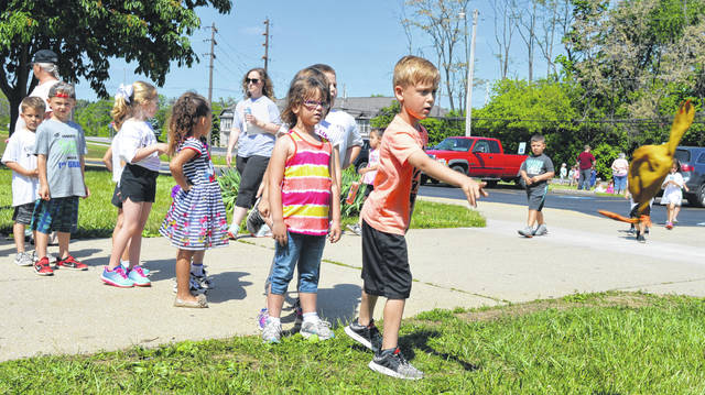 At a Field Day wrapping up the school year Wednesday, Holmes Elementary School children line up to toss a rubber chicken and a couple other items with the goal of landing them inside a plastic ring.