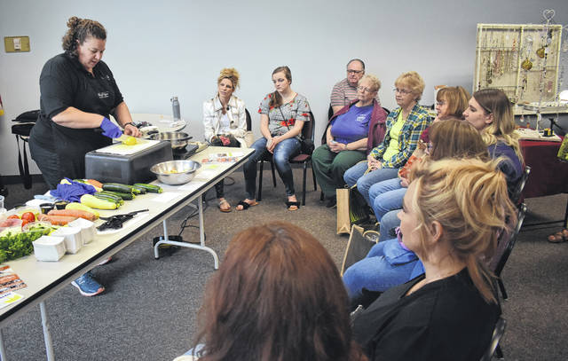Chef Jaime Carmody of Out Of Thyme Kitchen Studio shows Clinton County Farmers Market attendees on Saturday how to make zucchini fritters — one of several market-inspired dishes. To learn more about the market vendors and events during the Spring Market, www.clintoncountyfarmersmarket.com or follow it on Facebook.
